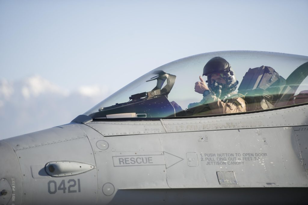 A view of a pilot in the cockpit of an American military jet. The pilot is giving the thumbs up sign with his left hand.