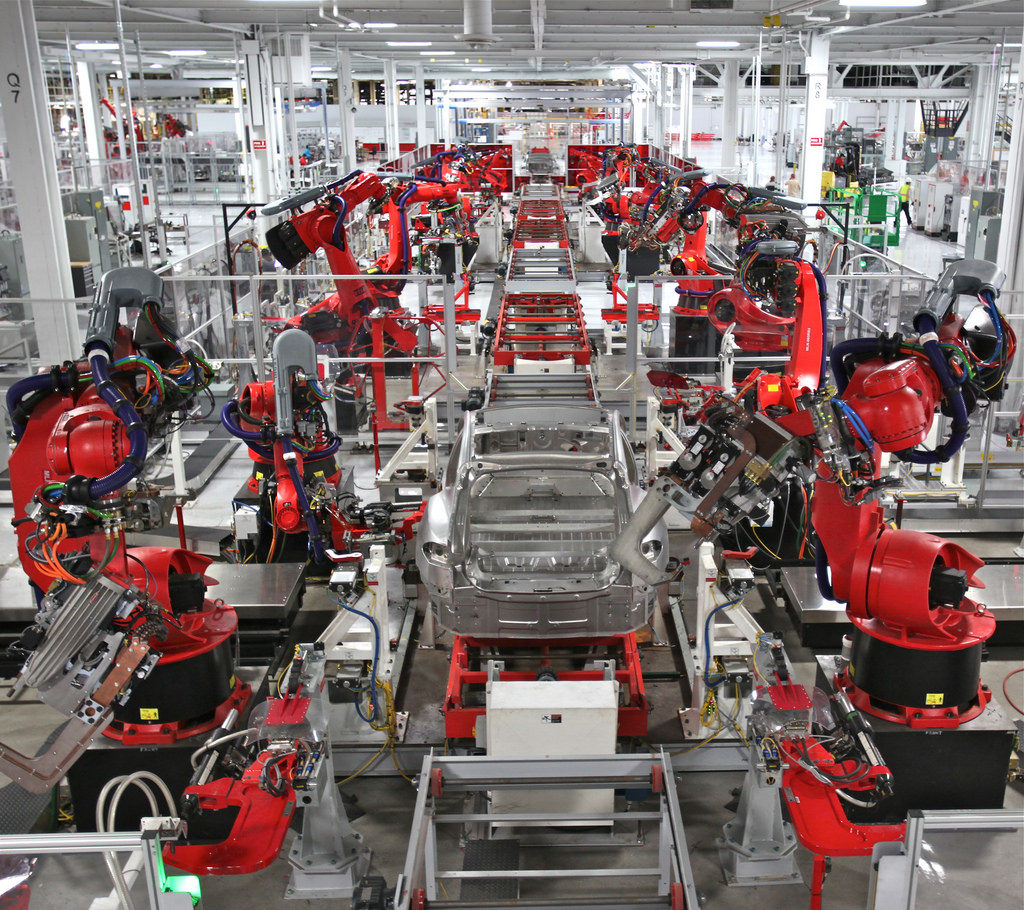 A view of the Frame line in the Tesla Model S factory. Many robots can be seen working on or prepared to work on the frame of the vehicle as it travels down a conveyor system in the center of the automation line.