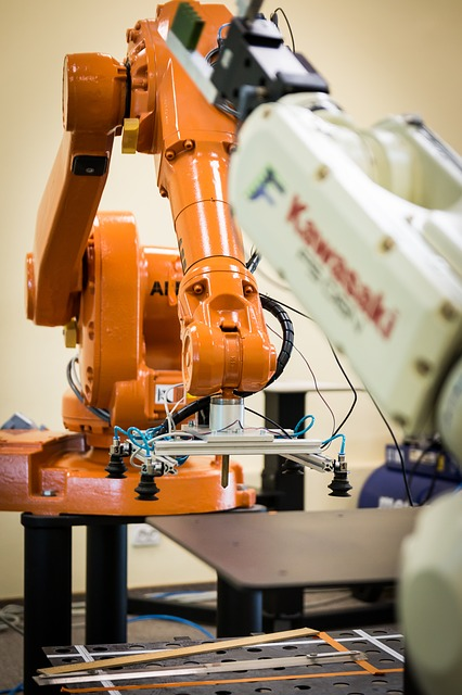 An image of two robots, one orange and one white. Image is used in an article describing the difference between robot technician and PLC technician.