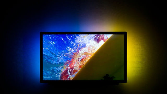 A colorful bias light behind a TV, with colors matching the imagery on a TV screen. Some of the best smart bias lighting is able to provide synchronized patterns like this on the wall behind your television.