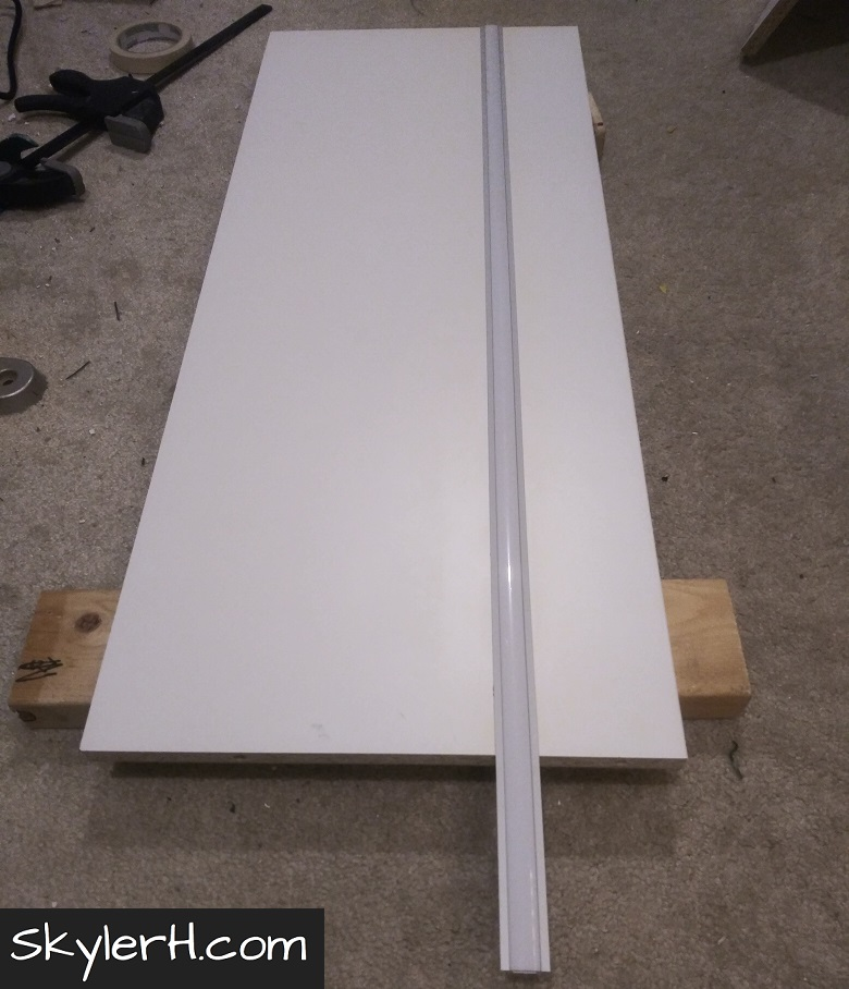 A white melamine shelf staged on the floor with LED channel inserted in a groove under the shelf. Once the channel is lined up, you can mark for your cut.